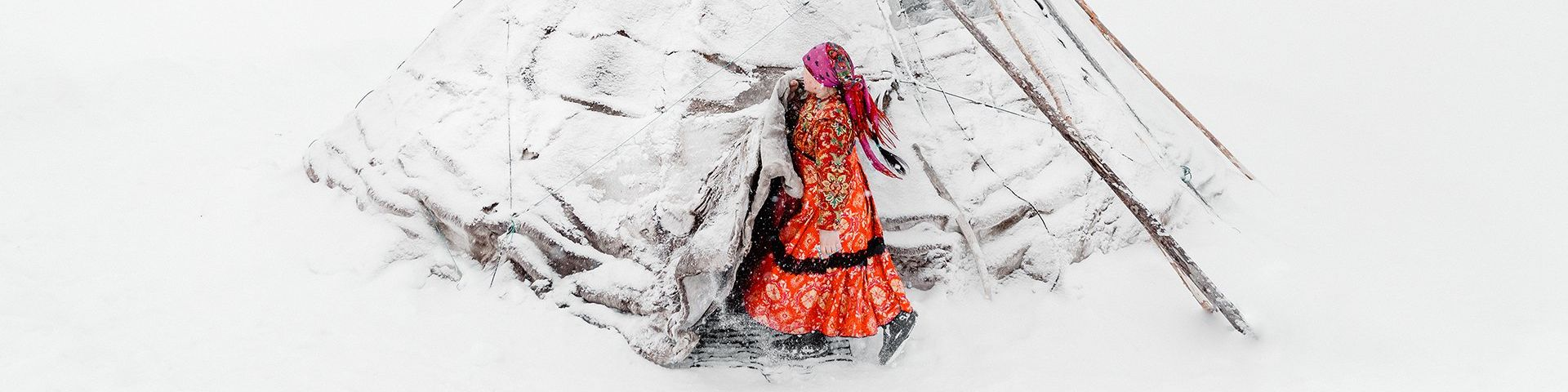 The image is dominated by pure white snow, save a snow-covered chum, or traditional tent used by the migrational tribes of the region. A woman emerges from her tent and is wearing a long orange/red patterned dress and boots. The dress has a black trim midway up the skirt and she also wears a pink headscarf, tied at the back of her head, which swings behind her.
